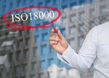De hand van jonge zakenman schrijft het woord ISO 18000 op wolkenkrabber royalty-vrije stock foto