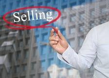De hand van jonge zakenman schrijft woord het Verkopen op wolkenkrabbers stock afbeelding