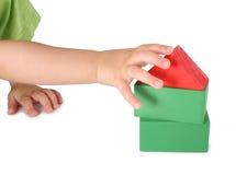 De hand van kinderen en stuk speelgoed huis van kubussen Royalty-vrije Stock Foto's