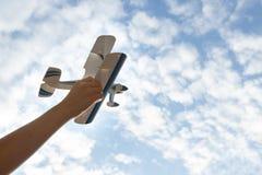 De hand van kinderen houdt een stuk speelgoed vliegtuig tegen de hemel, blauwe hemel witte wolken stock foto