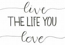 ` De hand van Live The Life You Love ` het van letters voorzien uitdrukking om mensen te motiveren om te doen van wat zij houden royalty-vrije illustratie
