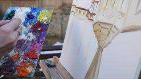 De hand van de meisjeskunstenaar het schilderen in oude stadsstraat stock video