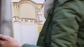 De hand van de meisjeskunstenaar het schilderen in oude stadsstraat stock footage