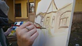 De hand van de meisjeskunstenaar het schilderen in oude stadsstraat stock videobeelden