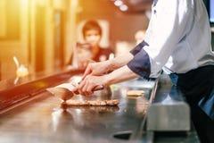 De hand van de mens neemt het koken van vlees stock foto