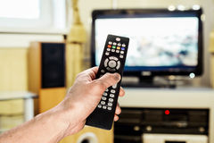 De hand van mensen verzendt de afstandsbediening op TV Stock Afbeeldingen