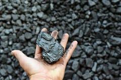 De hand van de mijnwerker toont steenkool in mijn stock fotografie