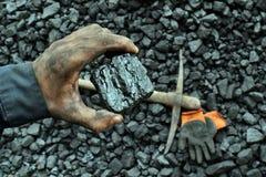De hand van de mijnwerker toont steenkool in mijn stock foto