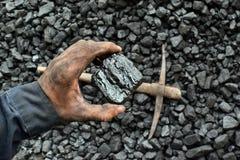 De hand van de mijnwerker toont steenkool in mijn stock afbeelding