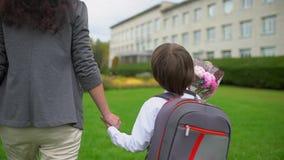 De hand van de moederholding van weinig zoon met rugzak die naar school in openlucht gaan, Eerstegraadsstudent, lage school, eers stock video