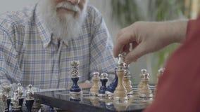 De hand van de onherkenbare mens bepaalt een schaakstuk Twee mensen het schudden overhandigt een schaakraad De mooie schaakreeks stock video