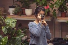 De hand van de persoon die het beeld van bloemen op de camera nemen stock afbeelding