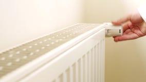 De hand van de persoon het aanpassen temperatuur op thermostaat aan controlehitte in centraal huis verwarmingssysteem stock video