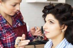 De hand van samenstelling het hoofd schilderen, maakt omhoog lopend De make-upkunstenaar past mascara op de wimpers van het model stock fotografie