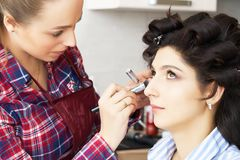 De hand van samenstelling het hoofd schilderen, maakt omhoog lopend De make-upkunstenaar past mascara op de wimpers van het model royalty-vrije stock afbeelding