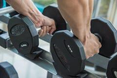 De hand van de sportmens houdt domoor, die het uitwerken uitoefenen bij de fitness Royalty-vrije Stock Fotografie