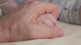 De hand van de vader en van de baby