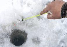 De hand van de visser die de hengel tijdens de winter houden een gat royalty-vrije stock fotografie