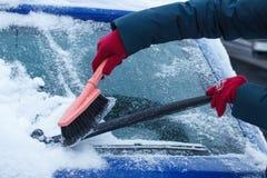 De hand van vrouw die borstel gebruiken en verwijdert sneeuw uit auto en voorruit Royalty-vrije Stock Fotografie