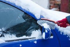 De hand van vrouw het gebruiken borstelt en verwijdert sneeuw uit auto, voorruit en spiegel Royalty-vrije Stock Fotografie