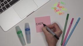 De hand van de vrouw het schrijven CHEMIE op blocnote stock footage