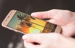 De hand van de vrouw houdt telefoon met de foto van de plaats van een droom stock afbeelding