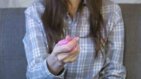 De hand van de vrouw kneedt, drukt en rekt een roze slijm uit Vrouwenspelen met slijm stock videobeelden
