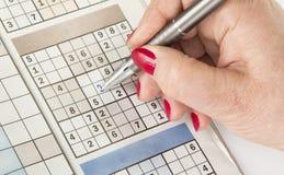 De hand van de vrouw met een pen vult sudoku in royalty-vrije stock fotografie