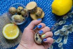 De hand van de vrouw met Pasen-manicure, vakantiedecoratie, aangestoken citroen, royalty-vrije stock foto's