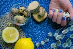 De hand van de vrouw met Pasen-manicure, vakantiedecoratie, aangestoken citroen, stock fotografie