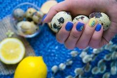 De hand van de vrouw met Pasen-manicure, vakantiedecoratie, aangestoken citroen, stock foto's