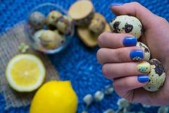 De hand van de vrouw met Pasen-manicure, vakantiedecoratie, aangestoken citroen, stock afbeeldingen