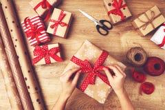 De hand van vrouw pakt dozen met Kerstmisgiften in royalty-vrije stock afbeeldingen
