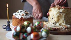 De hand van de vrouw snijdt een feestelijke Pasen op de keukenlijst naast een kerkkaars stock footage