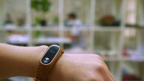 De hand van vrouw is vestigingsinstructies voor haar apparaat, geschiktheid bracelete, lichte bureauachtergrond, het actieve leve stock video