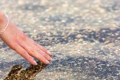 De hand van de vrouw voelt het koele water bij haar vingertoppen stock afbeeldingen