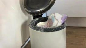 De hand van de vrouw zette één voor één gebruikte luiers in de vuilnisbak thuis stock videobeelden