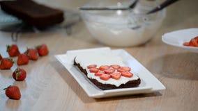 De hand van de vrouwelijke gebakjechef-kok maakt een heerlijke aardbeicake Kokend dessert in de keuken stock videobeelden
