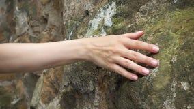 De hand van de vrouwentekening tegen oude steenmuur in langzame motie Vrouwelijke hand wat betreft ruwe oppervlakte van rots stock videobeelden