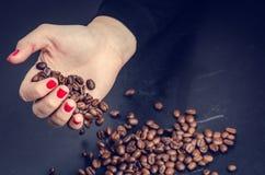 De hand van Womanhoudt koffiebonen op een donkere achtergrond Royalty-vrije Stock Foto