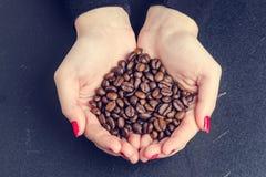 De hand van Womanhoudt koffiebonen op een donkere achtergrond Royalty-vrije Stock Fotografie