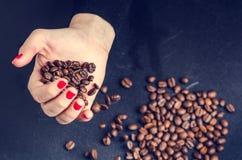 De hand van Womanhoudt koffiebonen op een donkere achtergrond Stock Afbeelding