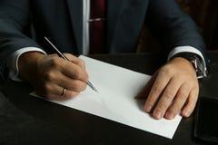 De hand van de zakenman schrijft met vulpenclose-up stock afbeeldingen