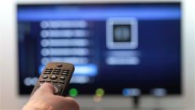 De hand verandert de kanalen op verre TV stock footage
