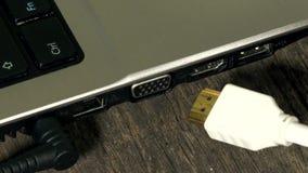 De hand verbindt kabel van de hdmi de hoge definitie met notitieboekjecomputer close-up stock videobeelden