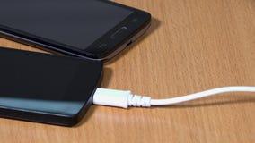 De hand verbindt witte en zwarte micro- usb kabels met slimme telefoons stock videobeelden