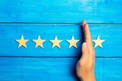 De hand verdeelt de vijfde ster van vier anderen Het schatten van 5 sterren, 4 sterren Overzicht van restaurant, hotel, koffie Stock Afbeelding