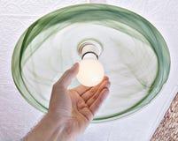 De hand verdraait energy-saving LEIDENE lamp op plafondlicht Stock Foto
