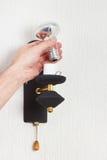 De hand verdraait gloeiende lightbulb in een lamp op witte muur Stock Afbeeldingen