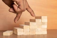 De hand vergelijkt bedrijfspersoon die direct van volledig van de houten stuk speelgoed trap op houten geweven achtergrond spring royalty-vrije stock afbeelding